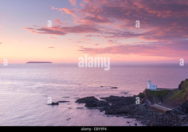 Hartland Point Lighthouse und Lundy Island unter einem farbenfrohen Sonnenuntergang, North Devon, England. Frühjahr Stockbild