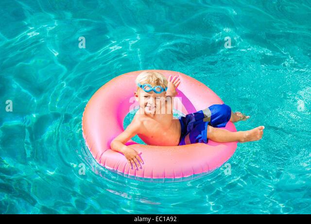 Junges Kind Spaß im Schwimmbad am Innenrohr Floß. Sommer Urlaub Spaß. Stockbild