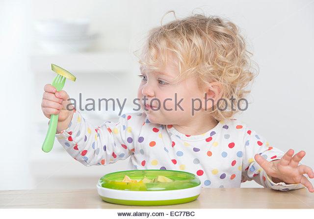 Neugierig Baby Essen Avocado mit Gabel Stockbild