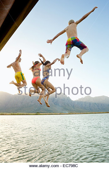 Familie, in Bademode, springen in einen See von einem Steg Stockbild