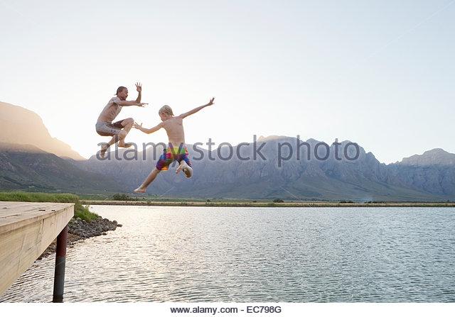 Vater und Sohn von der Anlegestelle in See springen Stockbild
