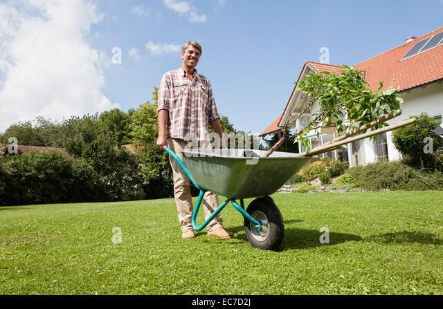 Mann mit Schubkarre im Garten Stockbild