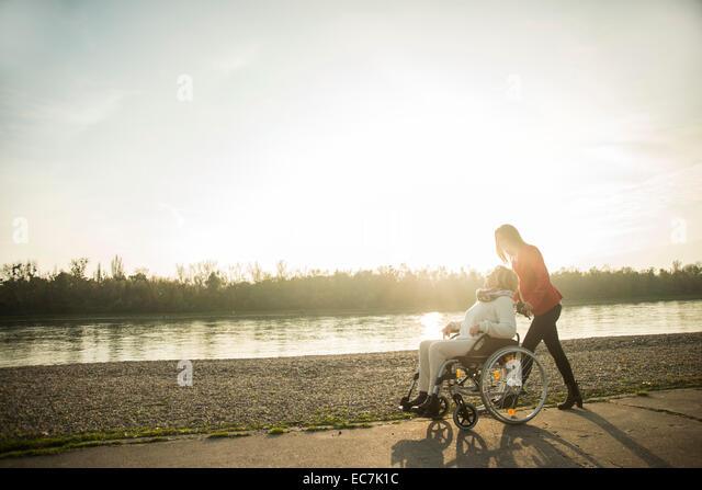 Erwachsenen Enkelin Unterstützung ihrer Großmutter im Rollstuhl sitzen Stockbild