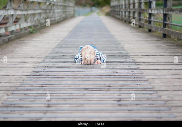Junge auf der Brücke nach unten durch Risse liegen Stockbild