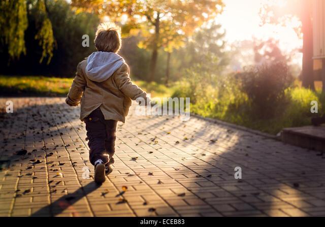 Junge läuft in Richtung der aufgehenden Sonne Stockbild