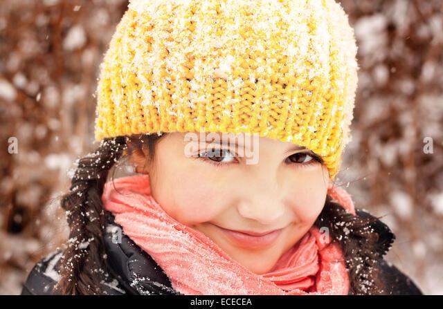 Hübsches kleines Mädchen (6-7) in Zöpfen und Hut, Lächeln bei Schneefall Stockbild