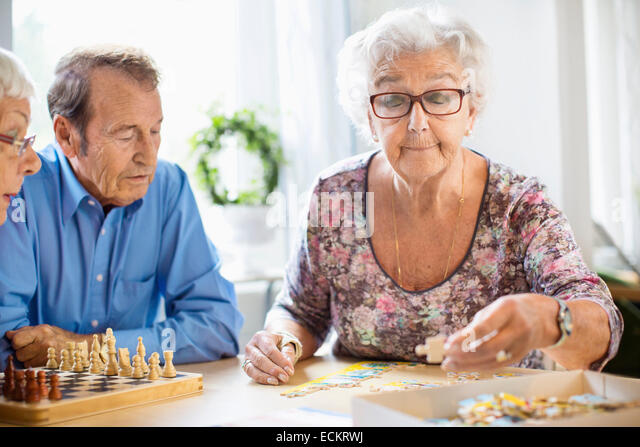 Ältere Leute spielen Freizeit am Tisch im Pflegeheim Stockbild