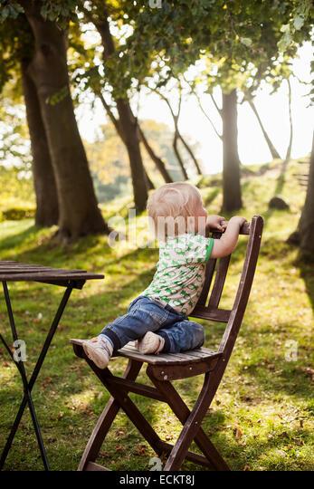 Volle Länge des jungen sitzen auf Holzstuhl im park Stockbild