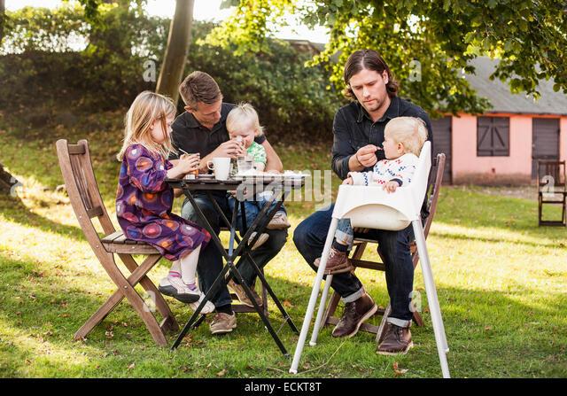 Voller Länge der Männer füttern Kinder im park Stockbild