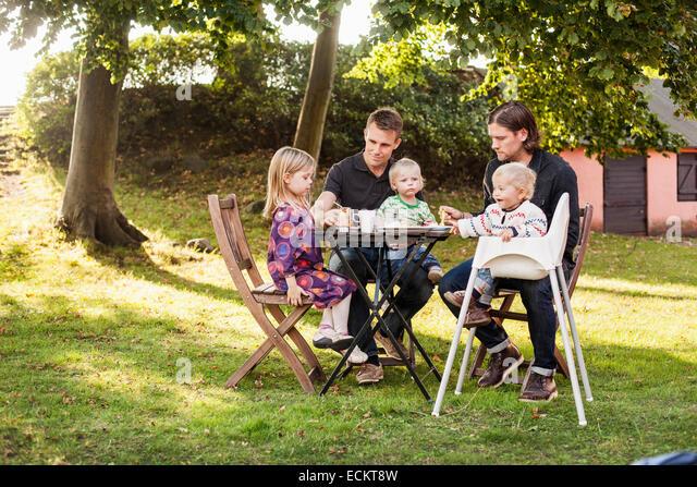 Gesamte Länge der Väter füttern Kinder im park Stockbild