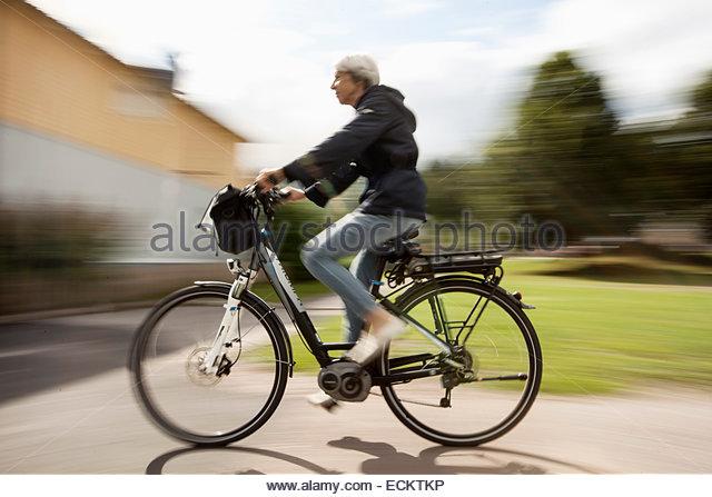 Bewegungsunschärfe senior Frau Radfahren auf Straße Stockbild