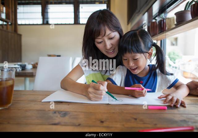 Mutter und Tochter sitzen an einem Tisch, zeichnen mit Filzstift Stifte, lächelnd. Stockbild