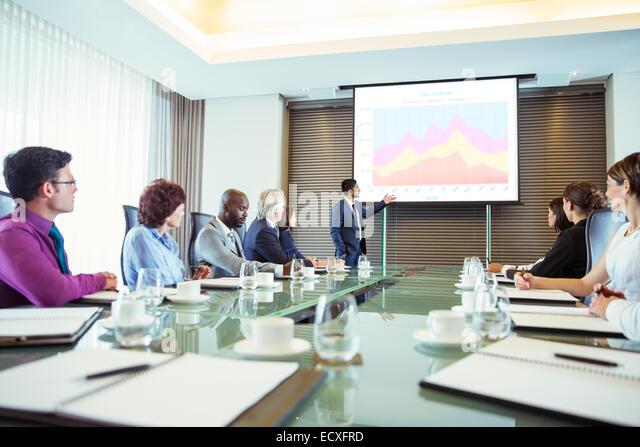 Multiethnische Gruppe von Menschen hören, Präsentation im Konferenzraum Stockbild
