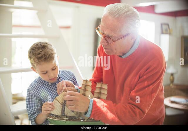 Großvater und Enkel bauen Modell Segelboot Stockbild
