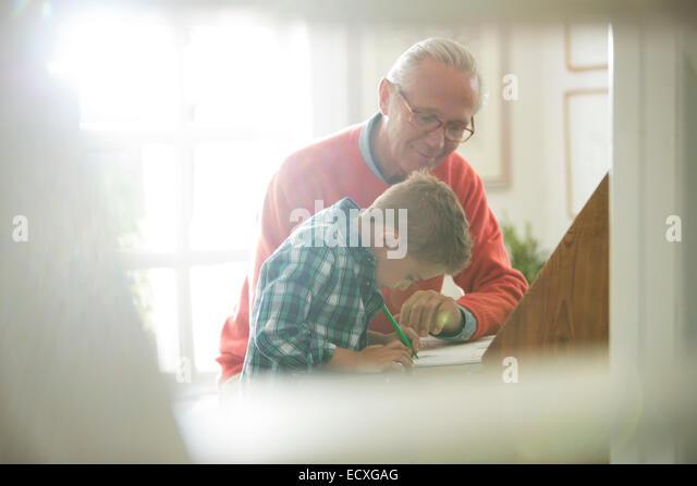 Großvater und Enkel schreiben am Schreibtisch Stockbild