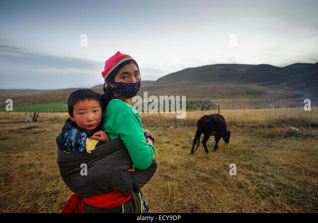 Tibetischen Mutter trägt ihren Sohn in einer Schlinge Stockbild