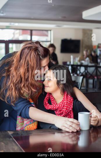 Mutter Tochter (6-7) auf Stirn im Café küssen Stockbild
