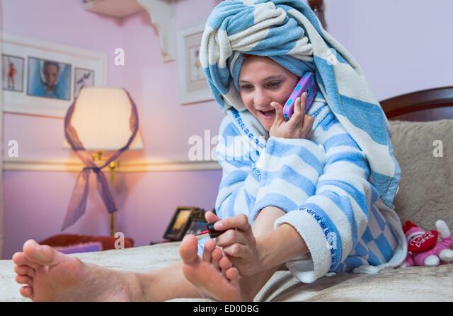 Junges Mädchen telefonieren mit Handy während der Malerei Zehennägel Stockbild
