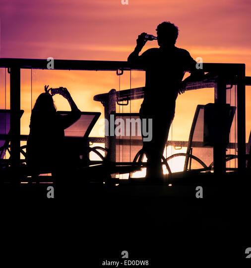 England, Southampton, Silhouetten von paar entspannende auf Balkon bei Sonnenuntergang Stockbild