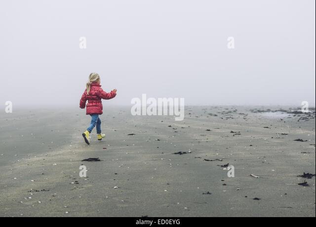 Mädchen läuft am Strand in Nebel, Ritthem, Zeeland, Holland Stockbild