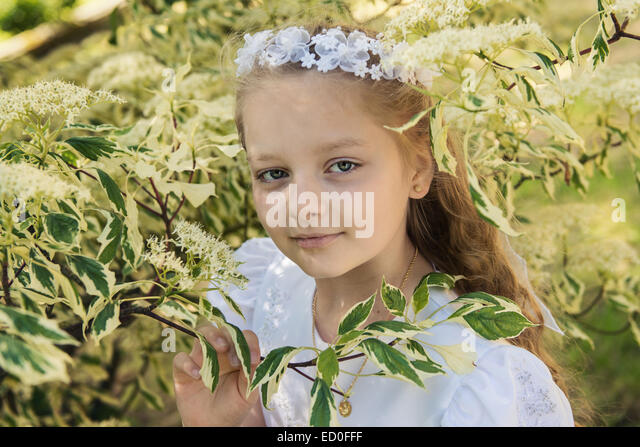 Erstes Kommunion Mädchen (8-9) zwischen Blätter Stockbild