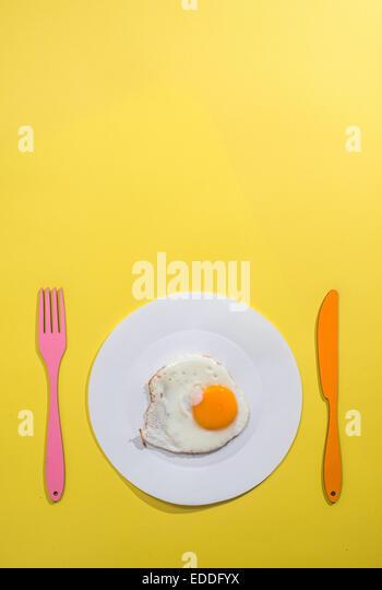Food-Konzept mit Papier, gebratenes Ei auf Teller, Gabel und Messer auf gelbem Hintergrund Stockbild