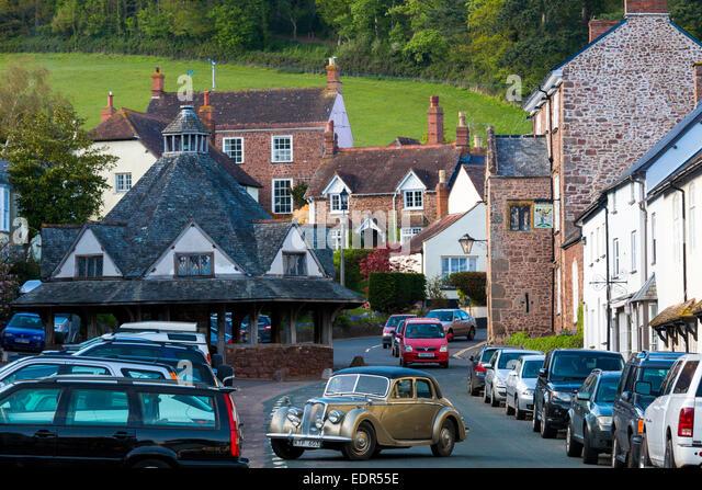 Autofahren in einem Oldtimer Riley 3 Liter Limousine durch die alte mittelalterliche Stadt Dunster, in Somerset, Stockbild