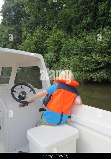 kleiner Junge Lenkung ein Boot Stockbild