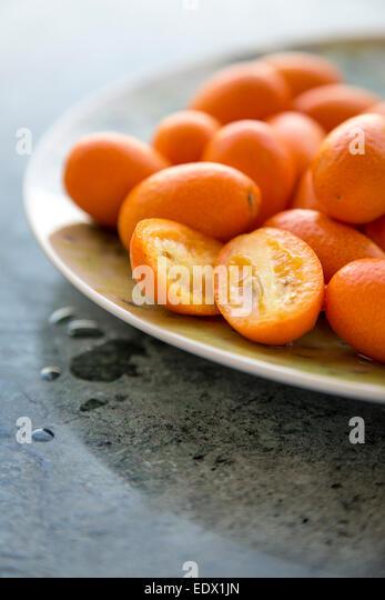Gruppe von Kumquats auf einer grünen Platte auf einer grünen Marmor Oberfläche Stockbild