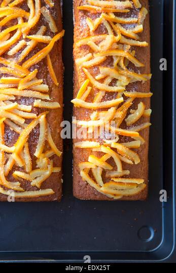 Home gebackene orange Kuchen auf Metalltablett mit Home gemacht herauskristallisiert Orangenschale topping Stockbild