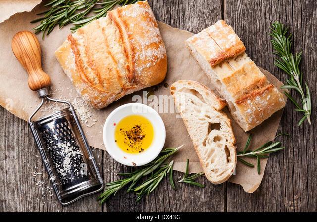 Geschnittenem Brot Ciabatta und Olivenöl extra vergine auf hölzernen Hintergrund Stockbild