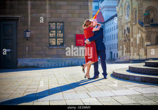 Älteres Paar küssen am Stadtplatz, München, Bayern, Deutschland Stockbild