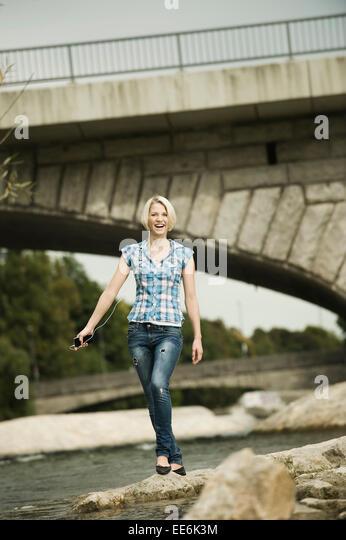 Junge Frau zu Fuß auf der Uferpromenade, München, Bayern, Deutschland Stockbild