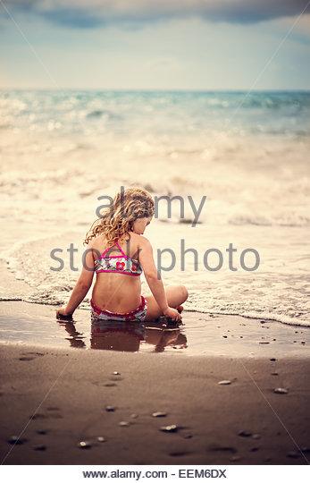Mädchen (4-5) sitzen am Sandstrand Stockbild