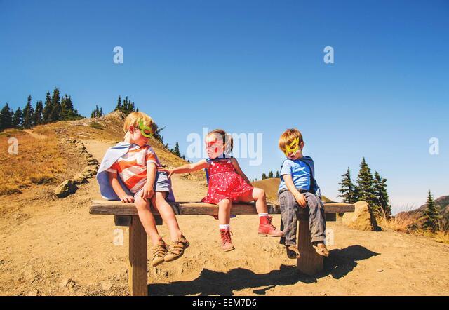 Drei Kinder (2-3, 4-5) sitzen auf Bank in Superhelden-Kostümen Stockbild