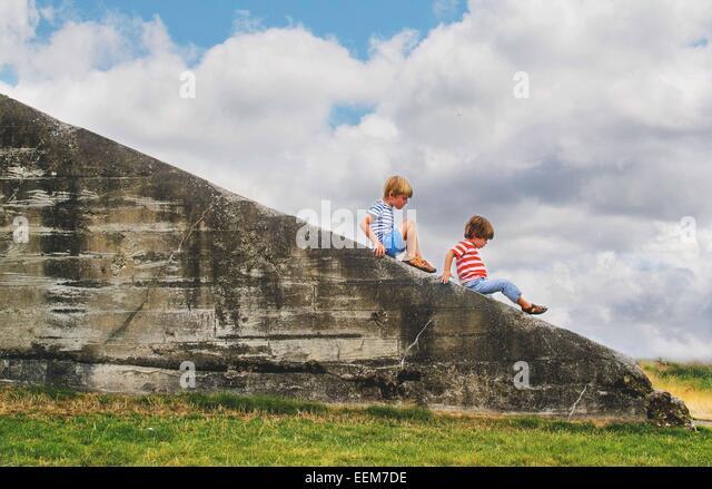 Zwei jungen (2-3, 4-5) klettern auf Felsvorsprung außerhalb Stockbild