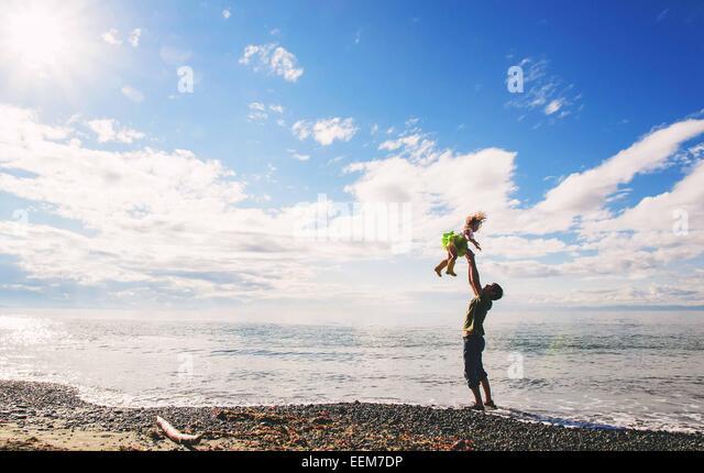 Vater werfen kleine Mädchen (2-3) bis in Luft am Strand Stockbild