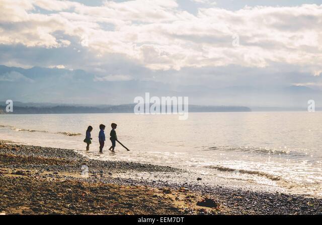 Drei Kinder (2-3, 4-5) stehen in der Silhouette am Strand Stockbild