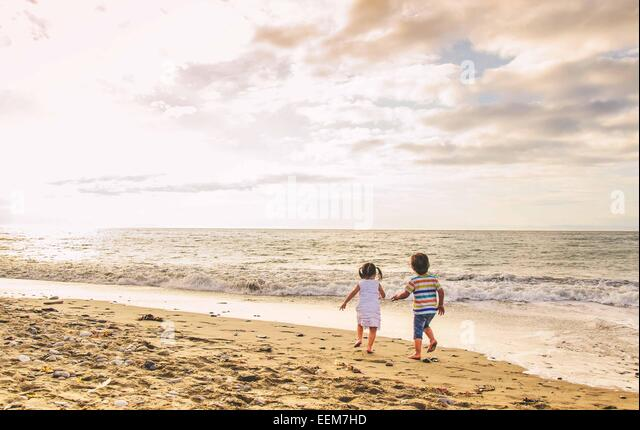Jungen und Mädchen (2-3) Hand in Hand zu Fuß am Strand Stockbild