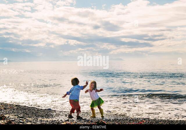 Jungen und Mädchen (2-3) tanzen am Strand Stockbild