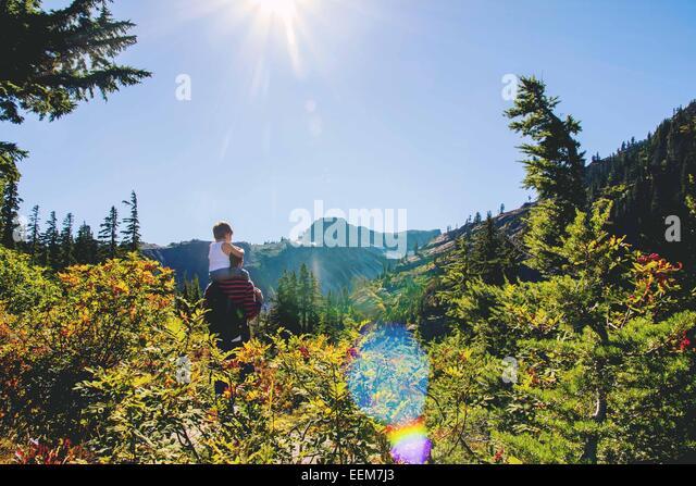 Jungen (2-3) sitzen auf Vaters Schultern Blick auf Berge Stockbild