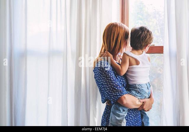 Mutter und junge (2-3) Kind aus Fenster Stockbild