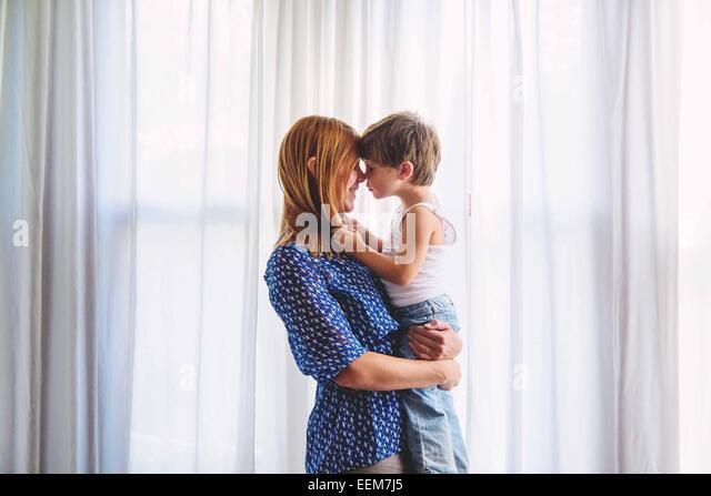 Mama hält junge (2-3) und Nasen berühren Stockbild