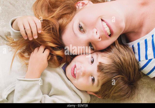 Mutter und Sohn (2-3) auf Boden liegend, Nahaufnahme Stockbild