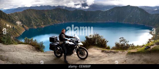 Ecuador, Mann auf dem Motorrad posieren gegen See am Laguna Quilotoa Stockbild