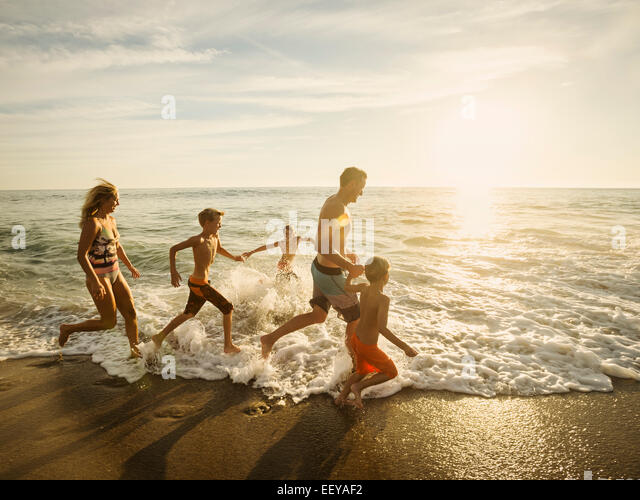 Familie mit drei Kindern (6-7, 10-11, 14-15) laufen am Strand, Laguna Beach, California, USA Stockbild