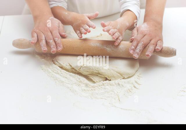Mutter und Tochter Hände kneten Teig auf dem Tisch. Stockbild