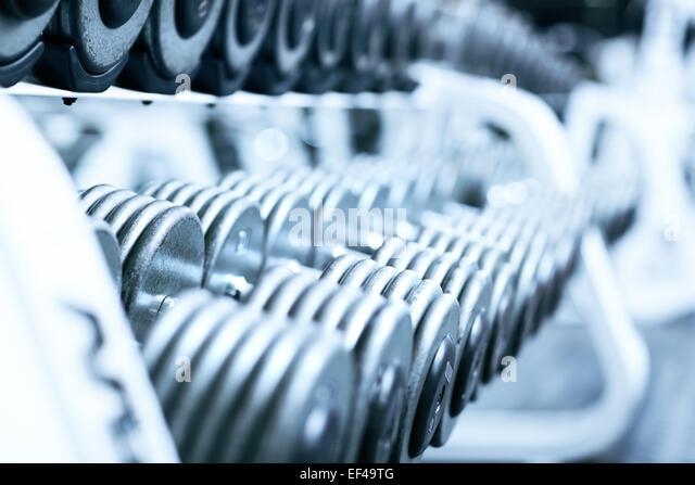 Hanteln im Fitnessstudio. Weiche blaue Tönung. - Stock-Bilder