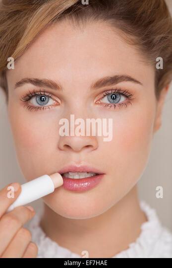 Schöne Frau Anwendung Lippenbalsam Stockbild