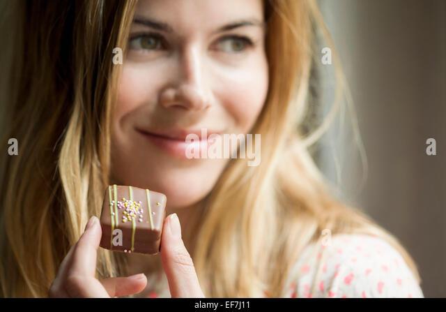 Frau eine Schokolade zu essen Stockbild